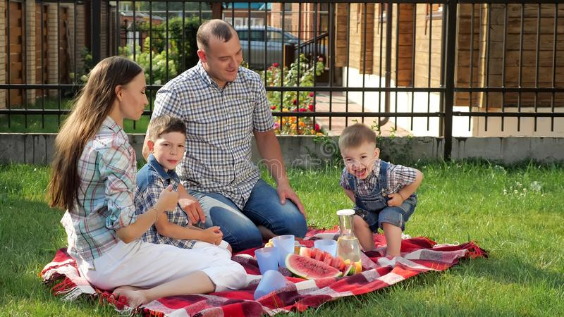 Happy family sits on blanket and father pours orange juice royalty free stock images