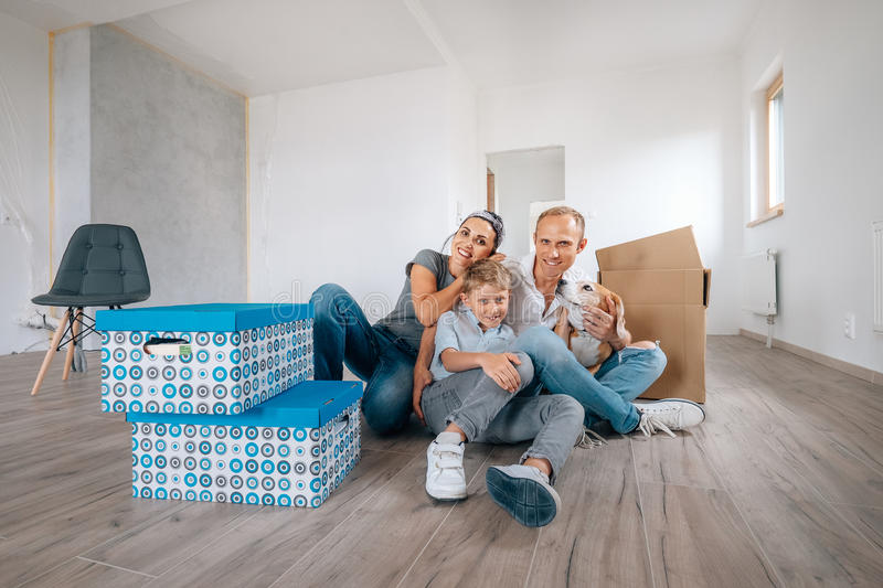 Happy family sits on floor in their new home stock photo