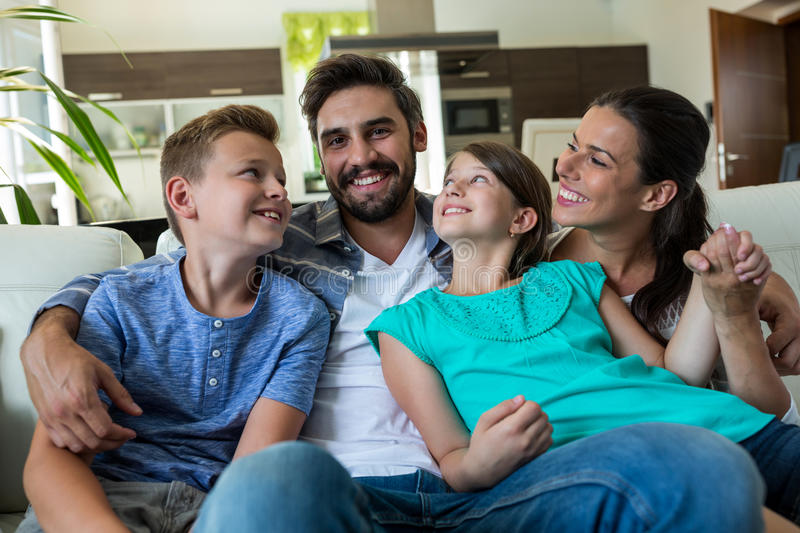Happy family sitting with arm around on sofa. At home stock images