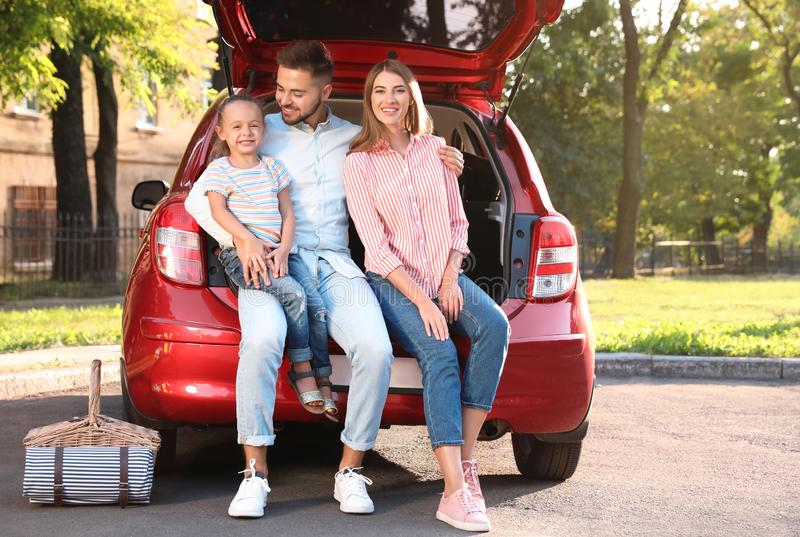 Happy family sitting in car`s trunk stock photography