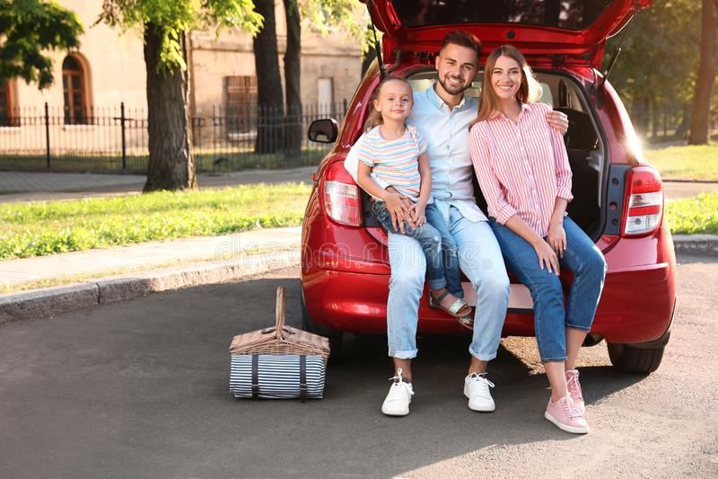 Happy family sitting in car`s trunk royalty free stock photo