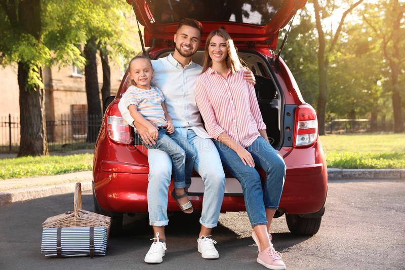 Happy family sitting in car`s trunk stock image
