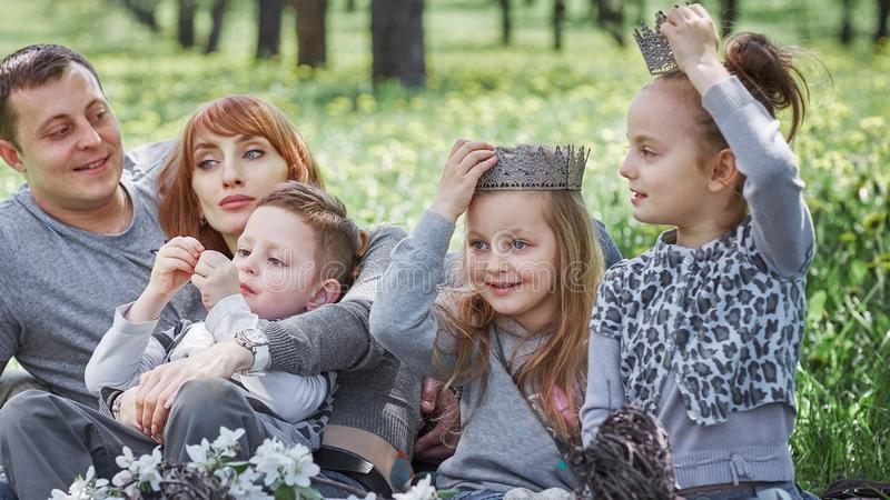 Happy family sitting in a clearing during a picnic royalty free stock photos
