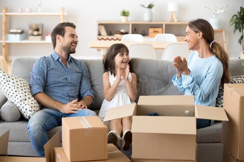 Happy family sitting on couch at new home. Young multi-ethnic family celebrate move at new modern wealthy home sitting together on couch in living room laughing stock images