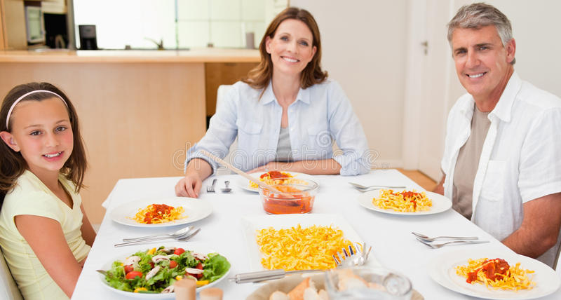 Happy family sitting at dinner table stock photo