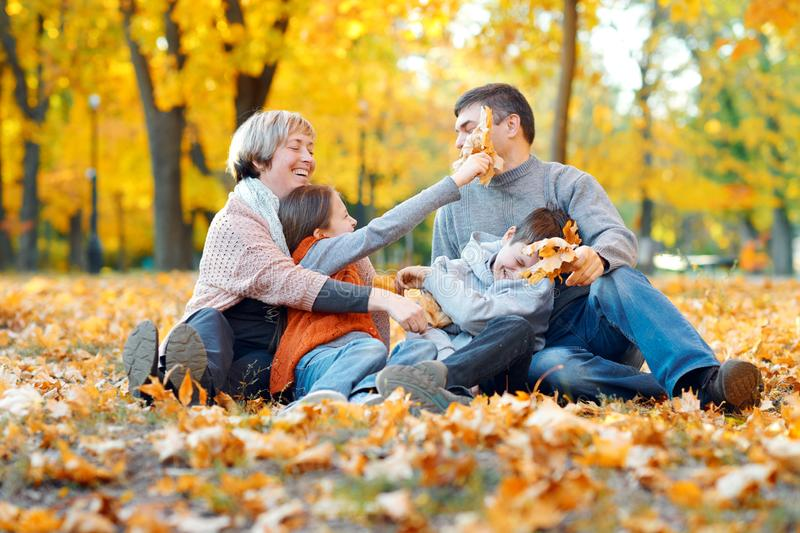 Happy family sitting on fallen leaves, playing and having fun in autumn city park. Children and parents together having a nice day royalty free stock images