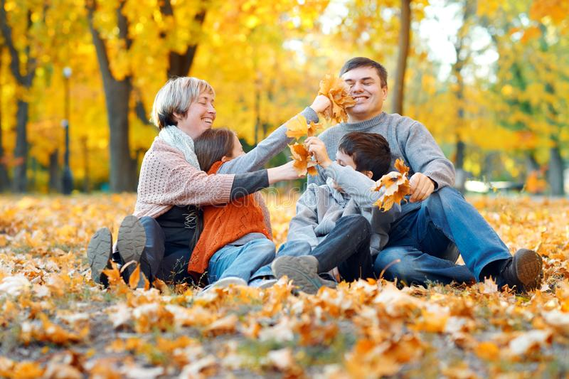 Happy family sitting on fallen leaves, playing and having fun in autumn city park. Children and parents together having a nice day stock photo