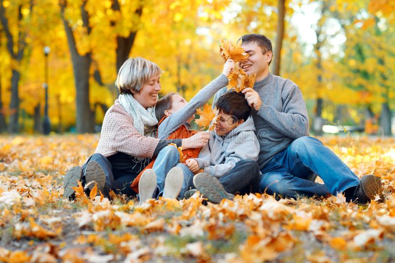 Happy family sitting on fallen leaves, playing and having fun in autumn city park. Children and parents together having a nice day royalty free stock photos