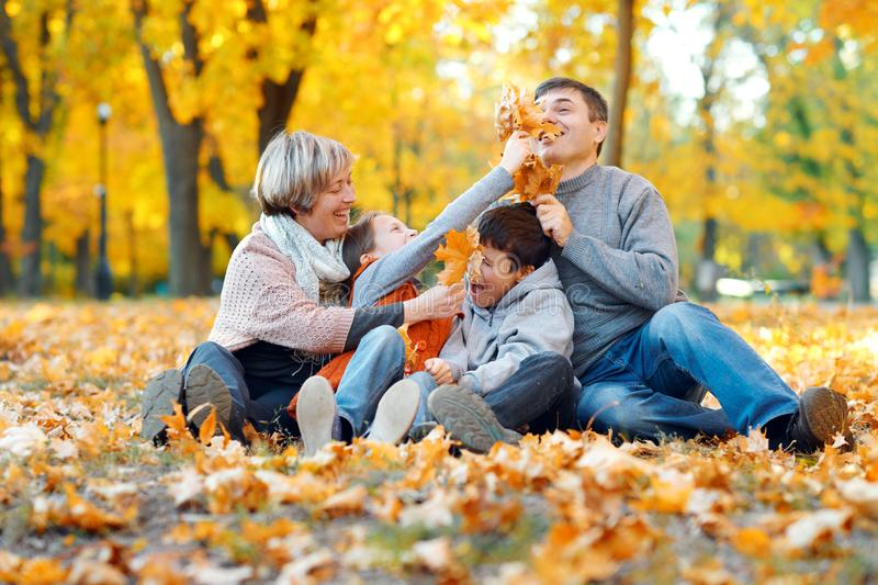 Happy family sitting on fallen leaves, playing and having fun in autumn city park. Children and parents together having a nice day royalty free stock photography