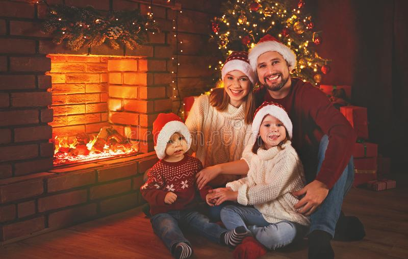 Happy family sitting by fireplace on Christmas Eve. Happy family father mother and children sitting by fireplace on Christmas Eve royalty free stock images