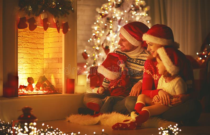 Happy family sitting by fireplace on Christmas Eve. Happy family father mother and children sitting by fireplace on Christmas Eve stock photos