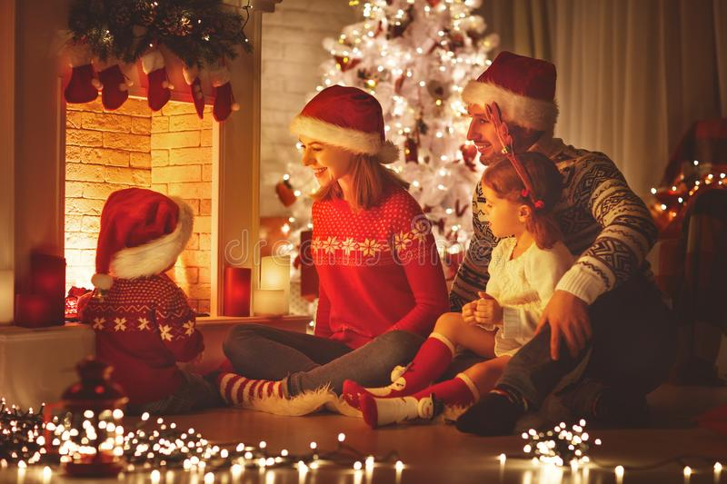 Happy family sitting by fireplace on Christmas Eve. Happy family father mother and children sitting by fireplace on Christmas Eve stock photography