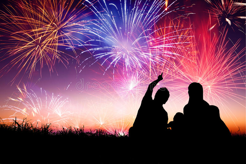 Happy family sitting on floor and watching the fireworks. Silhouette of happy family sitting on floor and watching the fireworks