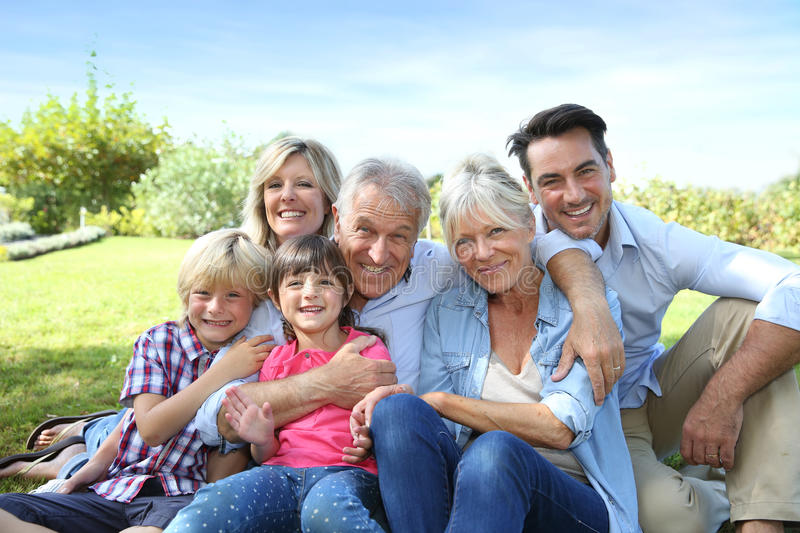 Happy family of 6 sitting in the garden royalty free stock image