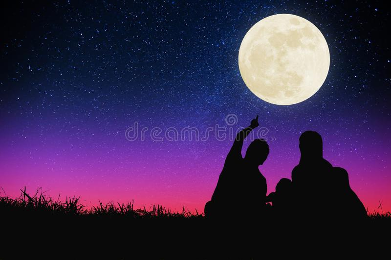 family sitting on hill and watching the moon and star .Celebrate Mid-autumn festival royalty free stock image