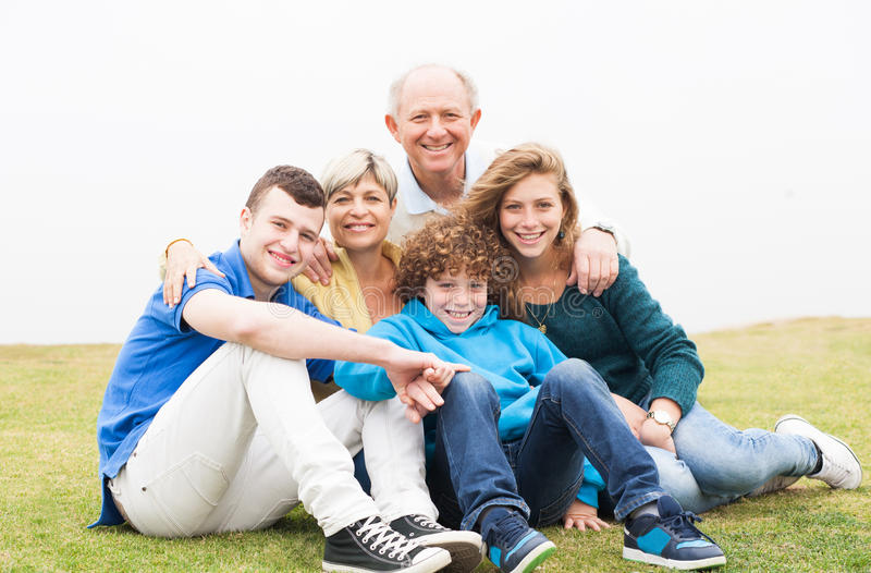 Happy family sitting in the lawn royalty free stock images