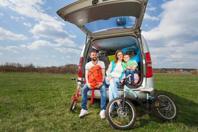 Happy family sitting in open luggage boot outside stock photo