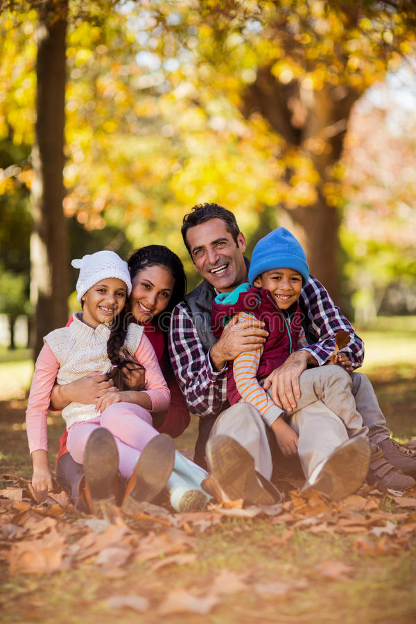 Happy family sitting at park during autumn royalty free stock photos