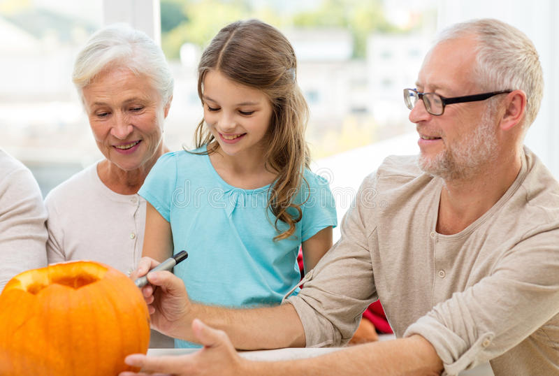 Happy family sitting with pumpkins at home. Family, happiness, generation, holidays and people concept - happy family making halloween pumpkins at home royalty free stock photo