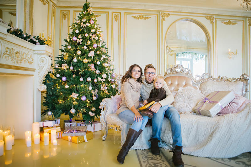 Happy family sitting on sofa near Christmas tree in a beautiful royalty free stock photo