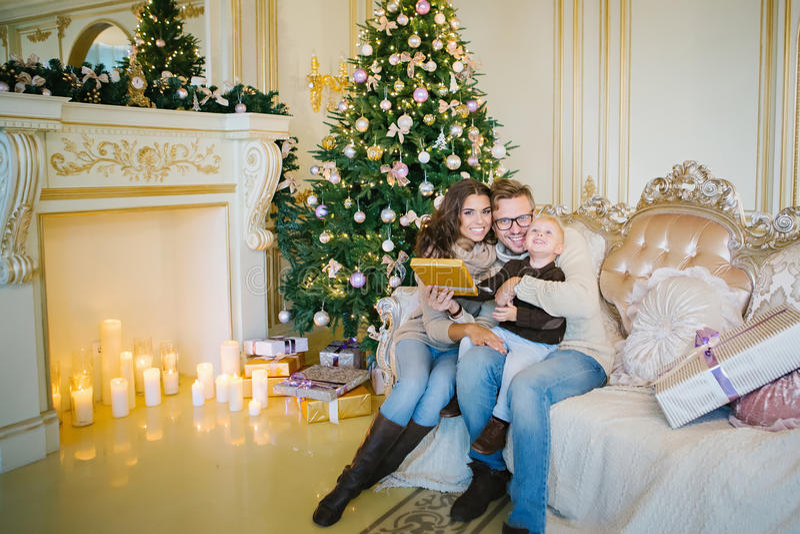 Happy family sitting on sofa near Christmas tree and fireplace royalty free stock photos