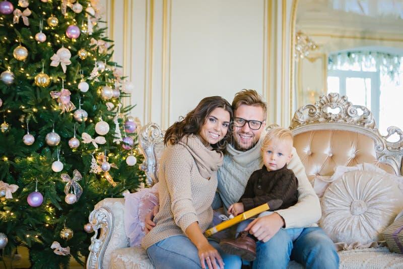 Happy family sitting on sofa near Christmas tree stock photography