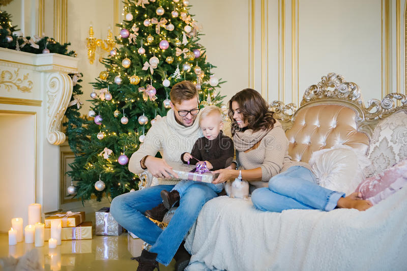 Happy family sitting on the sofa near the Christmas tree stock photos