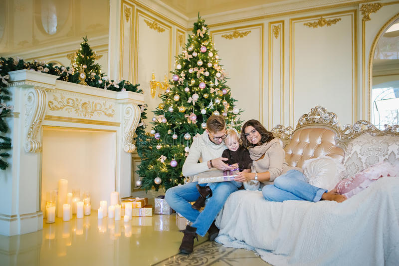 Happy family sitting on the sofa near the Christmas tree royalty free stock photography