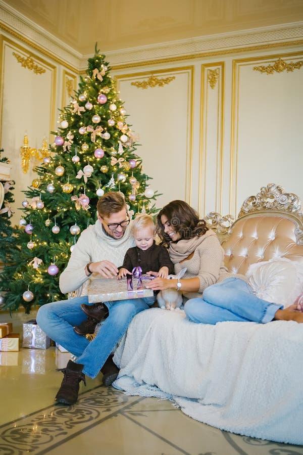 Happy family sitting on sofa near Christmas tree royalty free stock photo