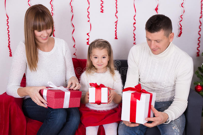 Happy family sitting on sofa and opening christmas gifts royalty free stock images