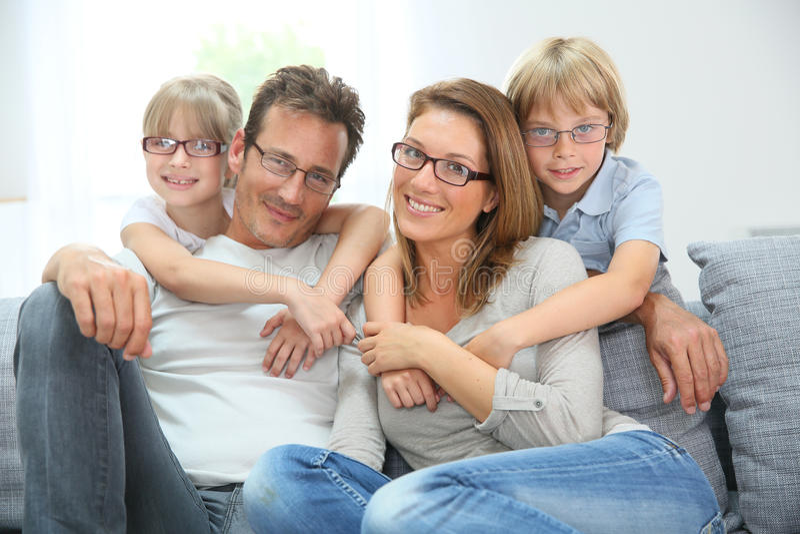 Happy family sitting on sofa wearing eyeglasses stock photos