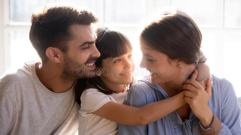 Happy family sitting together, little daughter and father embracing mother stock photo