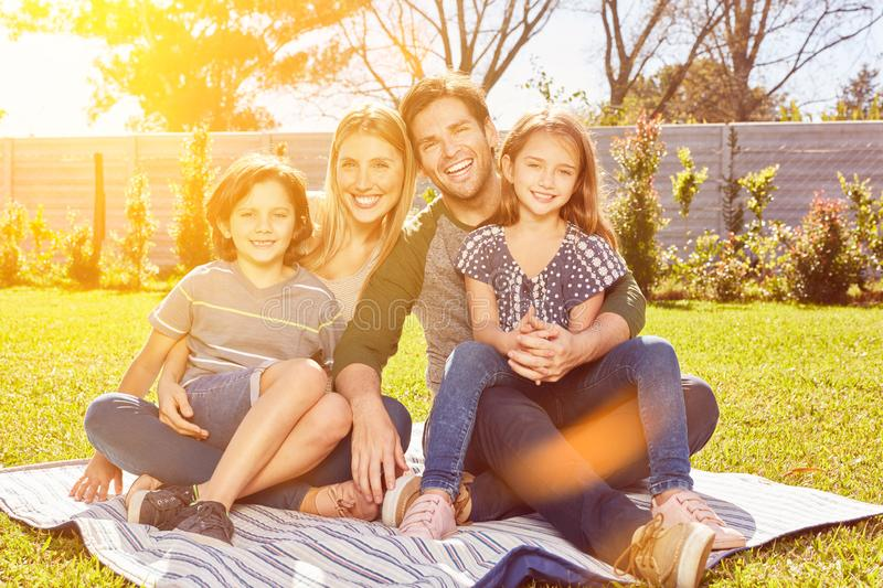 Happy family is sitting with two kids in the garden stock images