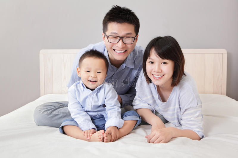 Download A Happy Family Sitting On White Bed Stock Photo - Image: 28910552