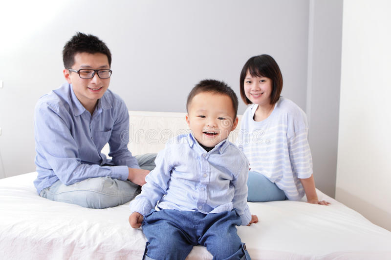 Download A Happy Family Sitting On White Bed Stock Photos - Image: 29312963