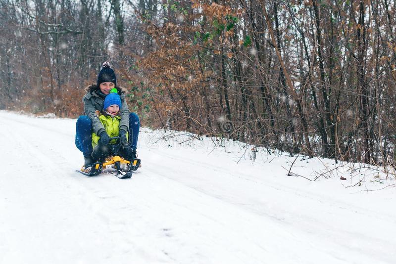 Happy family with sled in winter having fun together. Child sledding.Happy mother and her son enjoying sleigh ride. Family driving stock photos