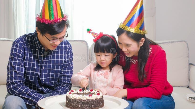Happy family with birthday cake. Happy family smile happily with birthday cake in the home stock photo