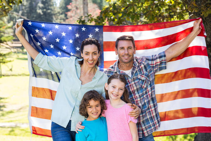 Happy family smiling with an american flag in a park royalty free stock photos