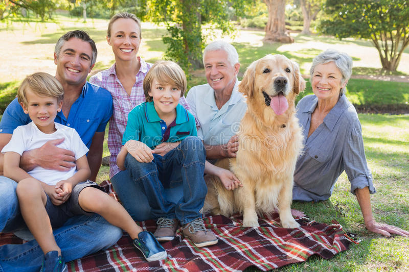 Happy family smiling at the camera with their dog. On a sunny day stock photos