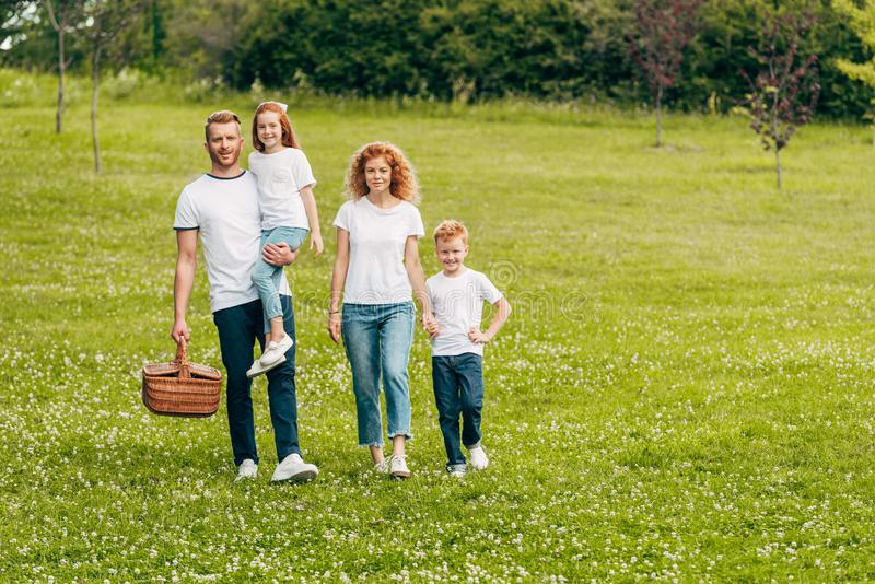 happy family smiling at camera while walking with picnic basket royalty free stock photography