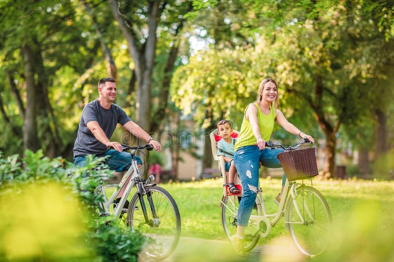 Happy family. Smiling father and mother with kid on bicycles having fun in park royalty free stock image