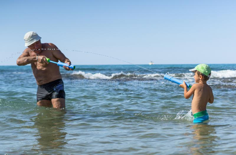 Happy family. Smiling grandfather and grandson playing at the sea. Positive human emotions, feelings, joy. At France beach. royalty free stock images