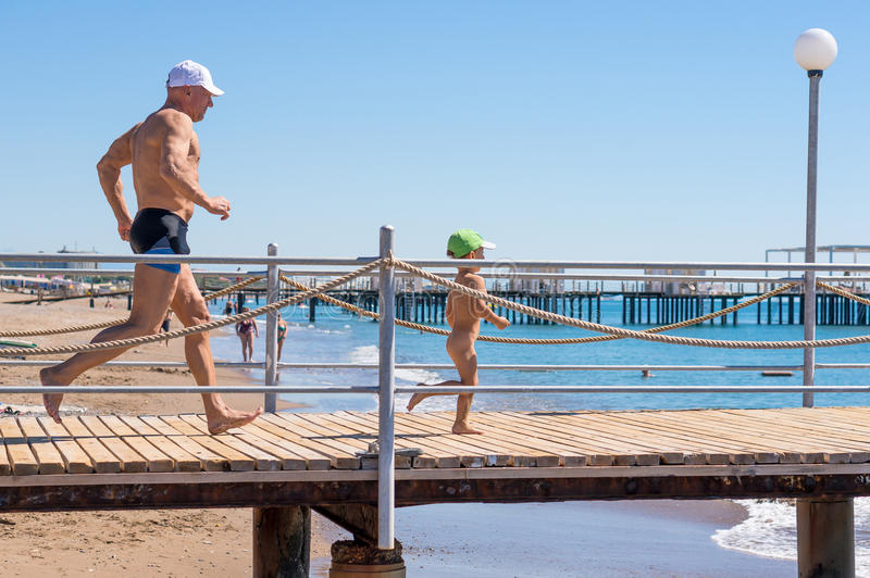 Happy family. Smiling grandfather and grandson playing at the sea. Running to the wave. Positive human emotions, feelings, stock photos
