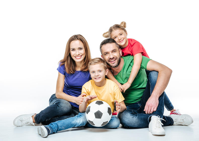Happy family with soccer ball. Happy family in colored t-shirts sitting together with soccer ball on white stock photo