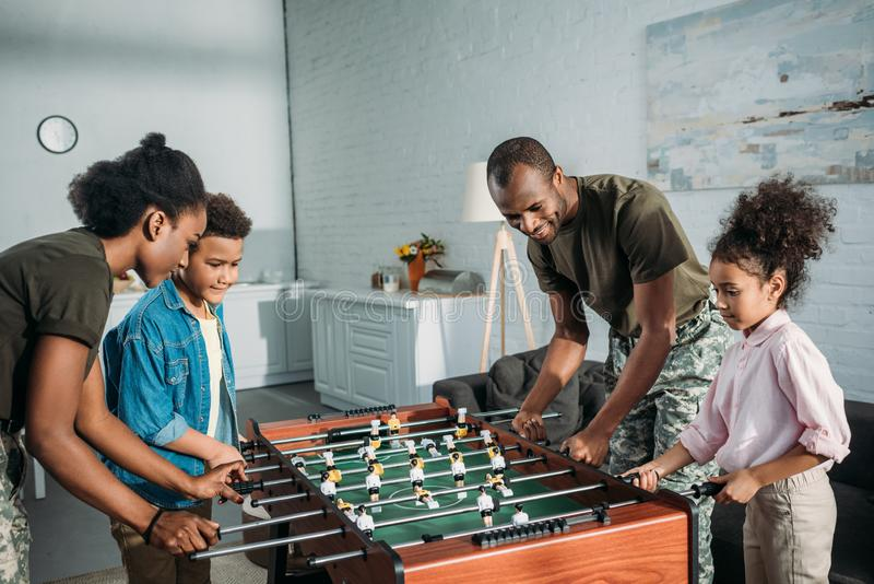 Happy family of soldier parents and african american kids playing. Table football stock photos