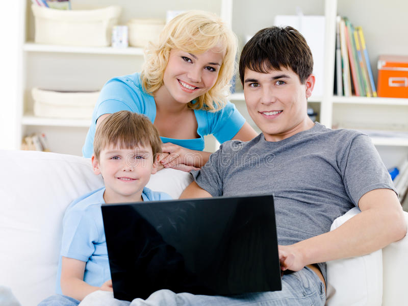 Happy family with son and laptop at home. Portrait of young happy cheerful family with son and laptop - indoors stock image