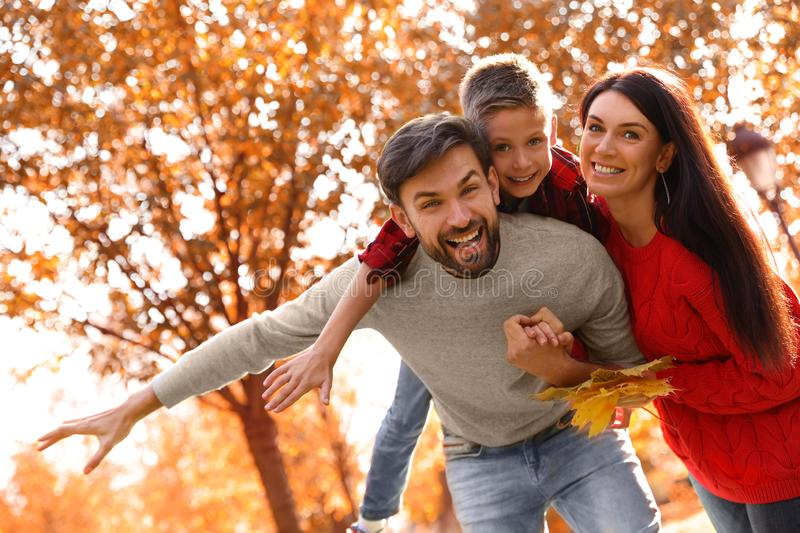 Happy family with son spending time. Autumn walk. Happy family with son spending time in park. Autumn walk stock images