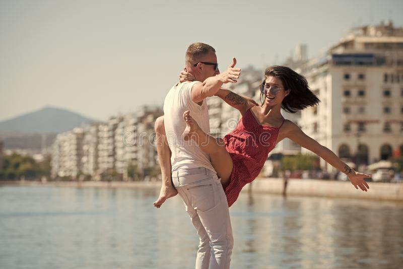 Happy family spend time together, dancing, having fun, sea and urban background. Couple in love stand on seafront. Family vacation concept. Man carries woman royalty free stock photo