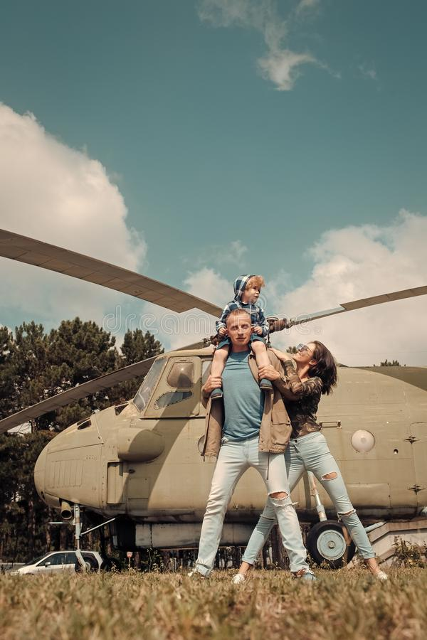 Happy family spend time together, on excursion, helicopter on background, sunny day. Family leisure concept. Mother and. Father and child walking in aviation royalty free stock photo