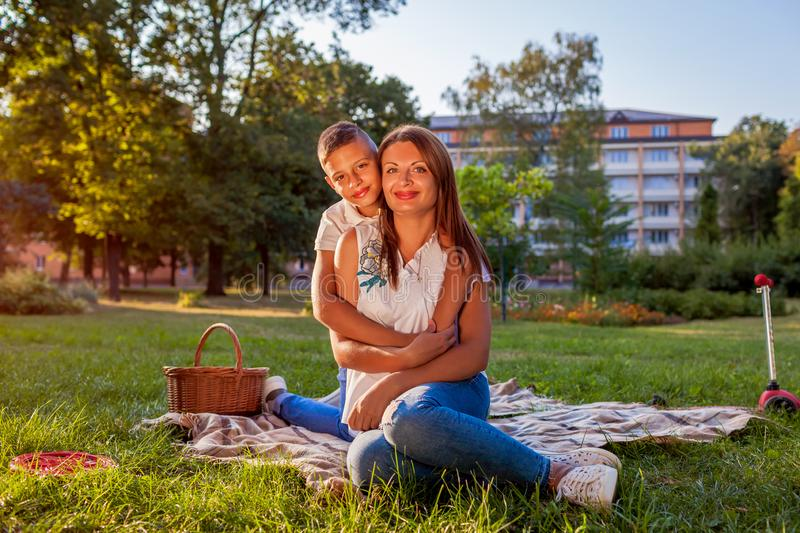 Happy family spending time outdoors having picnic in park. Mother with her son hugging and smiling. Family values stock photo